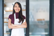 Asian Attractive Female Cafe Staff Wear Uniform Apron Smiling Cheerful Welcome To Cafe Reataurant With Confident And Happiness With Positive Service Mind After Lockdown Is Over In Shopfront Entrance