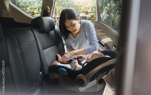 Fototapeta Asian young mother putting her baby son into car seat and fasten seat belts in t