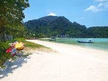 Tropical Beach, No People, Clean White Sand, Colorful Canoes On A Grass Of Coast Wait Tourists. Longtail Wooden Traditional Thai Boats Are In The Sea. Green Hill On A Horizon. Resort Of Thailand