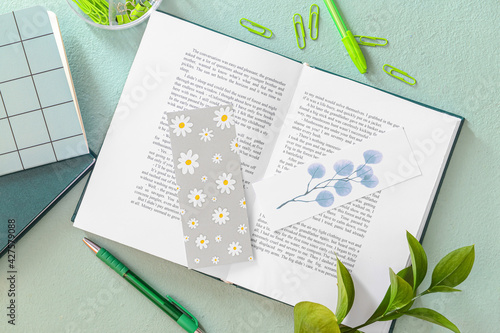 Obraz Book with bookmarks and stationery on color background - fototapety do salonu
