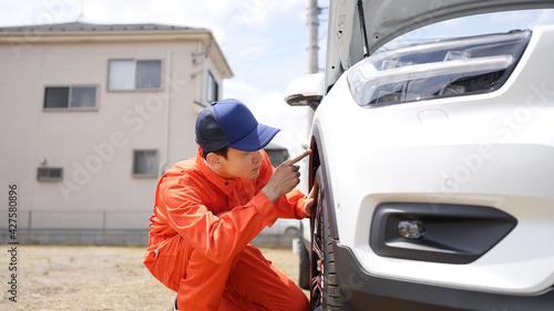 自動車のタイヤを点検する男性整備員