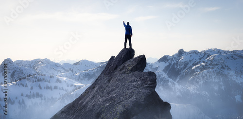 Composite. Adventurous Man Hiker on top of a Steep Rocky Cliff. over the Puffy Clouds. Sunset or Sunrise. Landscape Taken from British Columbia, Canada. Concept: Adventure, Explore, Hike, Lifestyle