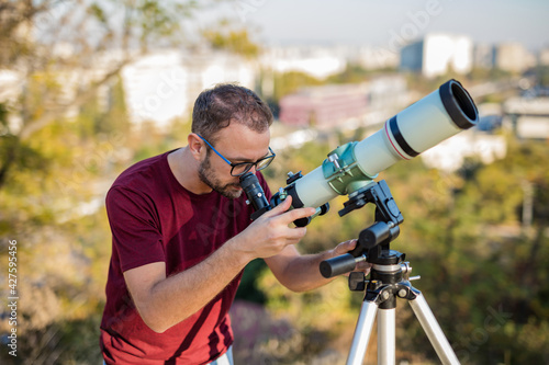 Fototapeta Amateur astronomer looking at the sky with a telescope.