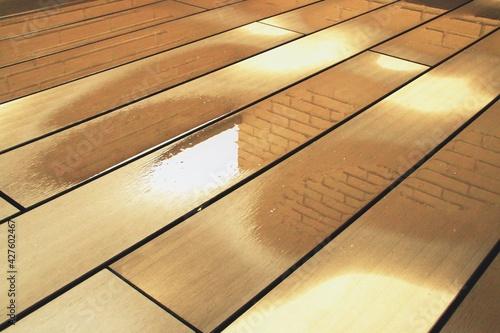 Charco de agua secándose tras la lluvia. Suelo de tablones de madera mojado.