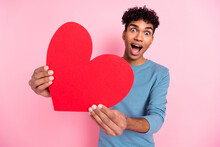 Photo Portrait Of Young Amazed Guy Showing Heart Shaped Postcard On Valentines Day Isolated On Pastel Pink Color Background
