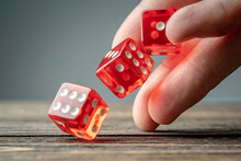 The Hand Is Throwing Red Dices On The Wooden Table. Concept Of A Casino And A Lucky Chance To Win
