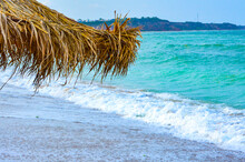 Close-up Of Straw Beach Umbrella Side On The Shoreline Of The Black Sea, Landscape With Blue Wavy Water In The Background, Summer Lifestyle.
