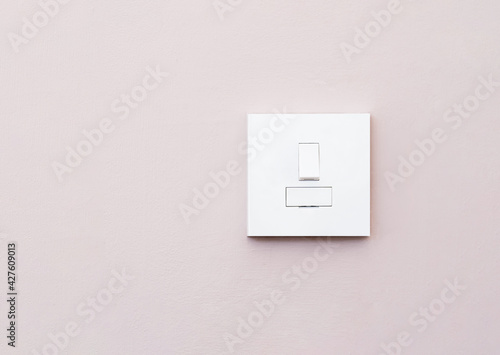 Fotografia Light switch isolated on light purple wall, A plastic mechanical switch of white color installed on wall for turn on or turn off the lights inside of the room