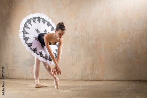 Fotografering Young ballerina in white tutu dancing in a spotlight in vintage scene
