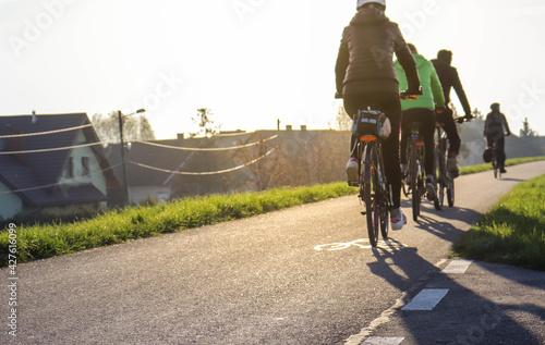 Młodzi ludzie jadą na rowerze w słoneczny dzień - fototapety na wymiar