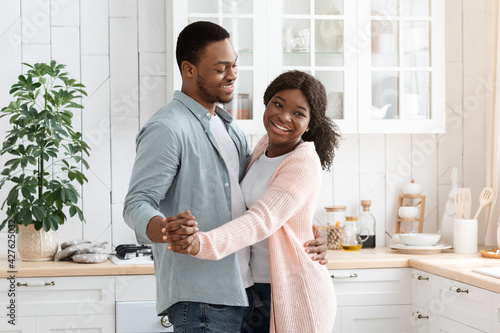 Billede på lærred Happy Cheerful Black Spouses Having Romantic Moments At Home, Dancing In Kitchen