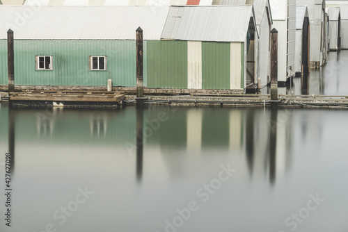 Billede på lærred Row of boathouses and their reflection in the river