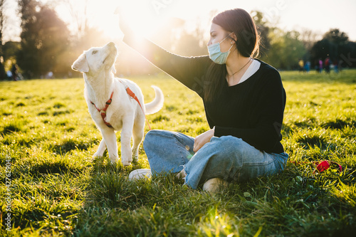 Young woman at the park at sunset plays and teaches behaviors to her dog wearing a face mask against Coronavirus infections, Covid-19 - Millennials having fun with her pet friends