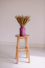 Bouquet Of Dried Herbs In Purple Colored Vase On Stool. Shades Of Beige. Minimalism Trendy Background. The Interior Detail Is Trend And Stylish. Hugge Accent. Ikebana On The Table. Grass Panicles Jar