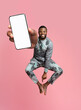 canvas print picture Excited black man in traditional African costume having fun, jumping up with cellphone on pink background, mockup