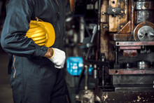 Asian Engineer Mechanic Man Checking And Holding Yellow Hard Hat For Maintenance Pressing Metal Machine At Factory, Worker At Industrial Working Concept