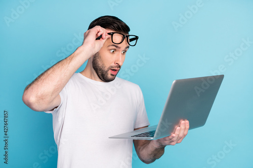 Fototapeta Photo of impressed man arm taking off glasses open mouth staring laptop isolated