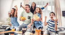 Family Watching Sports Match On Tv At Home, Cheering And Shouting Goal With Hands Up, Spilling Chips And Popcorn From Excitement
