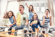 Raving Fans Cheering Sports, As Family Of Five Watch Football, Or Ice-hockey Match On The TV At Home, Screaming From Joy
