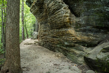 Sandy Trail Follows The Contour Of Overhanging Rock Wall