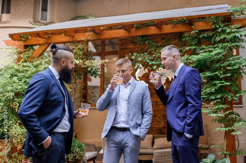 Fototapeta Front view of young groom with friends drinking whiskey and talking before wedding ceremony on the street. Concept of groom morning obraz