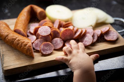 Fototapeta Dziecięca rączka sięgająca po kiełbasę z cebulą na desce do krojenia obraz