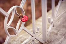 A Small Iron Lock In The Form Of A Red Heart Is Chained To The Fence Of The Bridge On A Brown Background. Wedding Ceremony As A Sign Of Loyalty And Well-being For Many Years. The Beloved Ritual.
