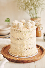 Vertical Shot Of A Raffaello Cake On A Wooden Tray With White Tablecloth Beneath