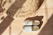 Textile Moccasins Made Of Natural Fabric Against The Background Of A Wicker Rattan Ottoman. Flatlay