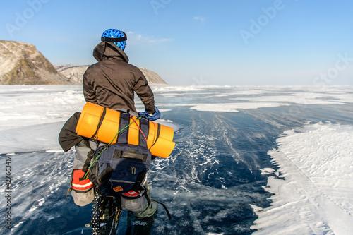 Fotografie, Obraz Byciclist on Baikal lake in winter on the sunset