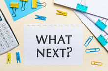 On A Light Background, There Are Stacks Of Documents, A White Calculator, Yellow And Blue Paper Clips And Clothespins, And A Notebook With The Text WHAT NEXT