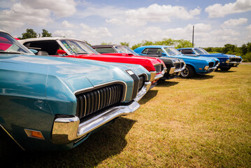 Vintage classic muscle cars parked together in field for sale or club cruise or car show