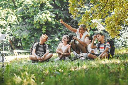 Foto Group of school kids sitting on grass in forest with they teacher