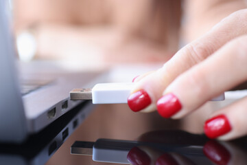 Female hand inserts USB flash drive into laptop connector