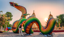 Rainbow Carve Serpent Or Colorful Thai Naga And Asian Woman Standing In The Sunset At Wat Phra That Nong Bua Temple
