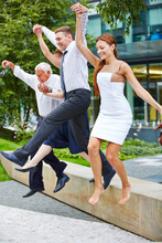 Full Length Of Happy Business People Jumping From Wooden Seat
