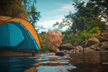Surface Level View Of Tent By Water In Forest