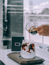 Pouring Black Coffee Into Glass With Ice