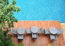 Poolside Wicker Chairs Outdoor Swimming Pool With Umbrella In Resort Hotel.