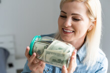 Woman Holding A Transparent Jar Full Of American Dollars. Shopping Concept
