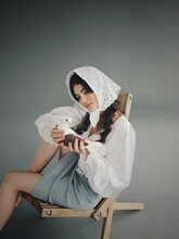 Woman Holding Umbrella While Sitting On Chair