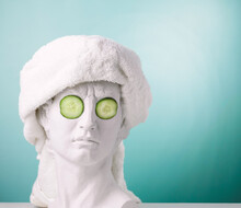 Plaster Statue Head Blue Background Wearing White Towel And Cucumber Face Mask. Beauty Care Concept.