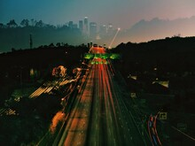 High Angle View Of Highway Light Trails At Sunset Against Cityscape
