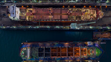 Aerial View Container Ship And Oil In Shipyard For Repair At Night. Can Use For Shipping