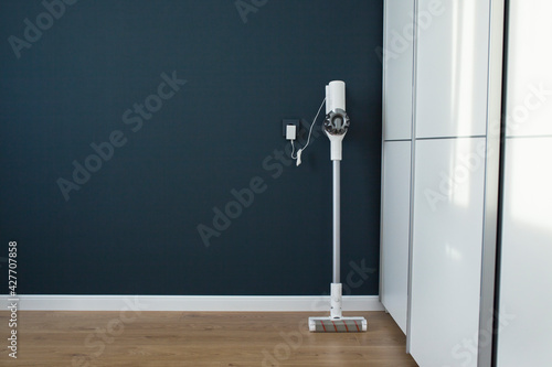 Obraz Modern cordless vacuum cleaner charges against a blue wall. Minimalistic interior. - fototapety do salonu