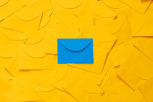 Yellow Envelopes Scattered On A Table , With Space For Text On A White Paper And A Blue Envelope Highlighted, Top View