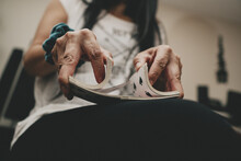 Low Angle View Of Woman Shuffling Cards On Lap.
