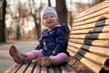 Girl Sitting On Wood Bench In Park