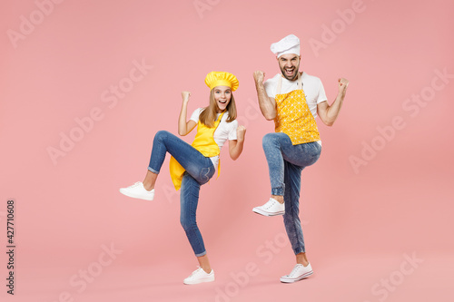 Full length teen fun girl dad man father's helper chef cook confectioner baker in yellow apron cap do winner gesture celebrate clench fist with raised legs isolated on pink background studio portrait Fototapet