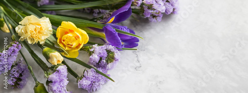 Fotografie, Obraz Yellow narcissus flowers and purple irises in a line floral arrangement isolated on marble background